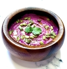 bright fuchsia ube tahini in a wooden bowl, garnished with cilantro and pepitas