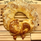 challah with sesame seeds on top, shaped like a wreath with a bow