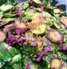 close-up of beet greens salad garnished with salt-cured egg yolk shavings