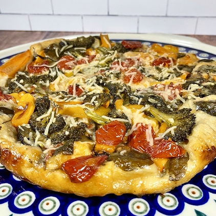 Close-up of vegan cast iron skillet pizza with vegan cheese, peppers, broccoli, scallions, mushrooms, tomatoes, and spinach