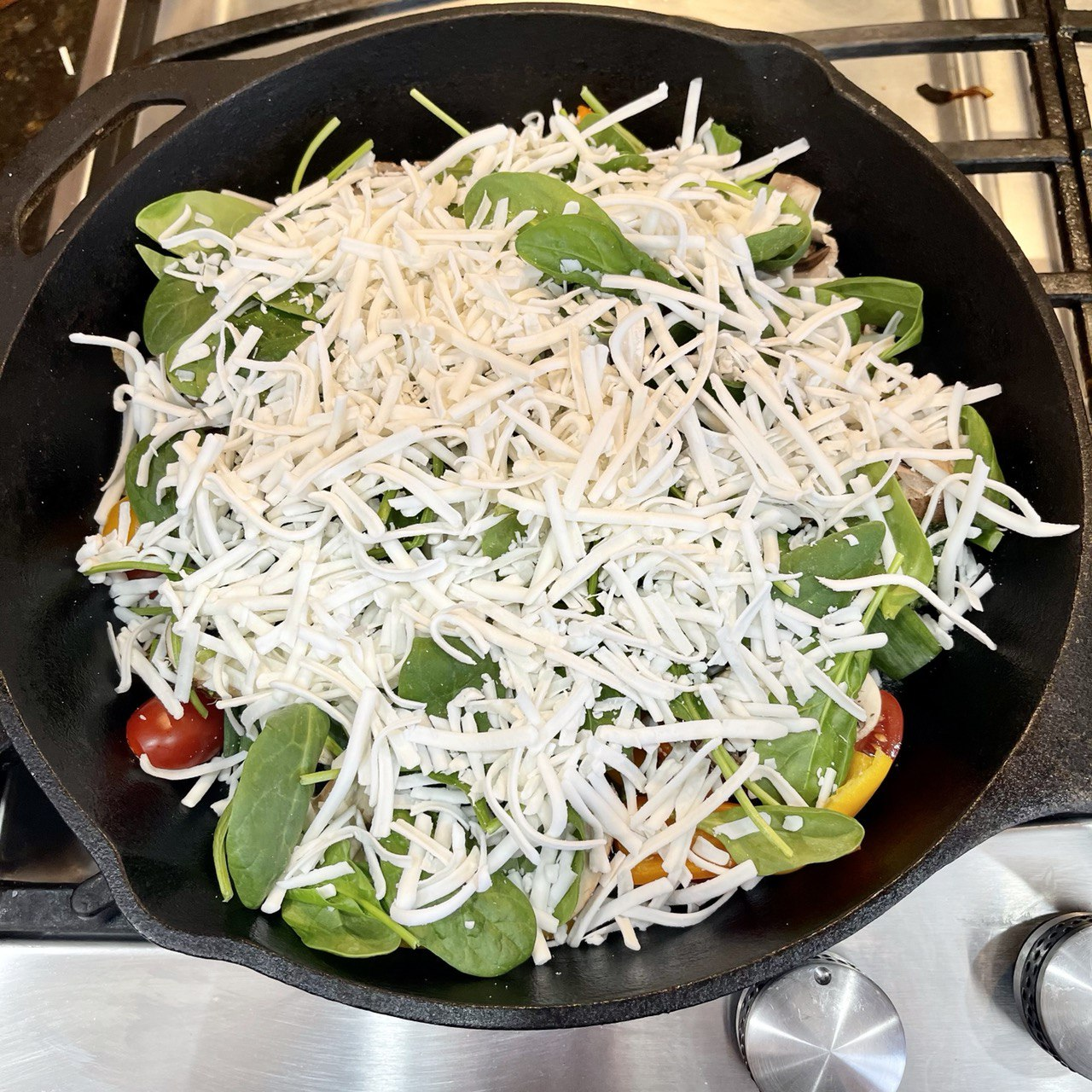 close-up of vegan mozzarella cheese sprinkled evenly over the previously-placed toppings in a 12 inch cast iron skillet