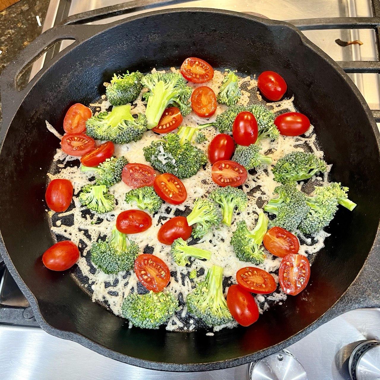 close-up of vegan parmesan cheese under cherry tomato halves and broccoli floret halves