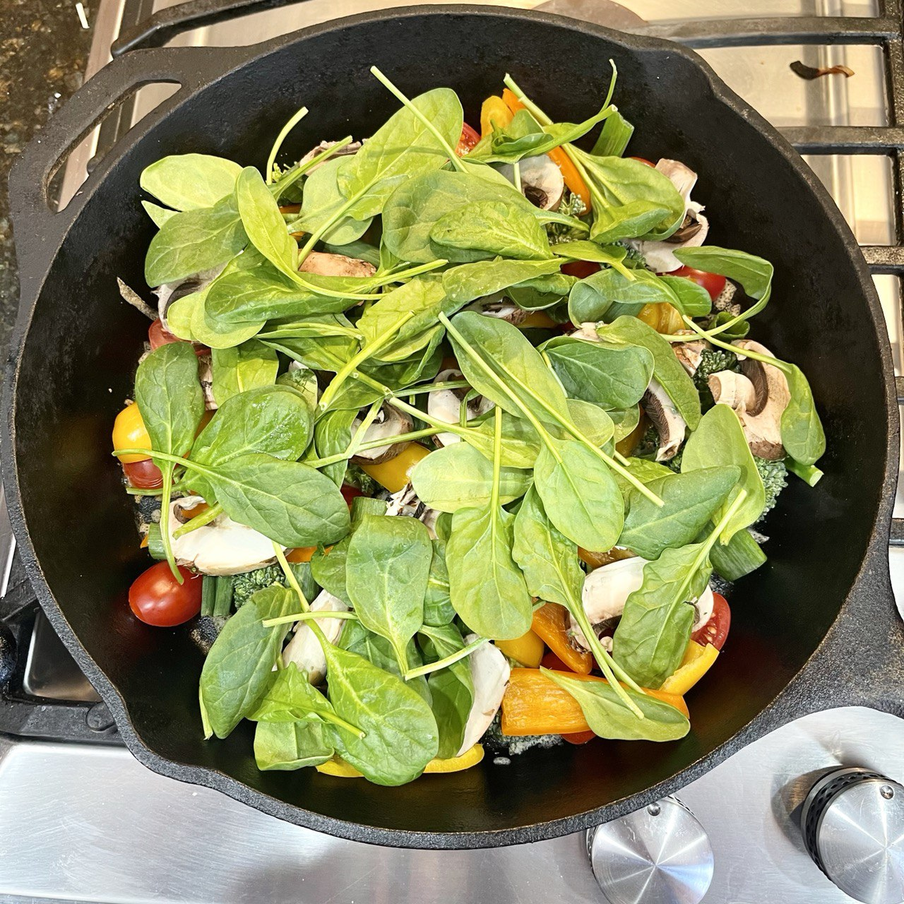 close-up of baby spinach leaves sprinkled evenly over the previously-placed toppings in a 12 inch cast iron skillet
