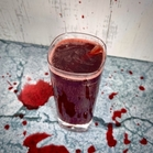 The Bloody Doorpost in a tall glass garnished with a cinnamon stick, with splatters of the drink in the background to make it look gory