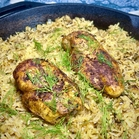 one-pan chicken and rice cooked in a cast iron skillet and garnished with dill