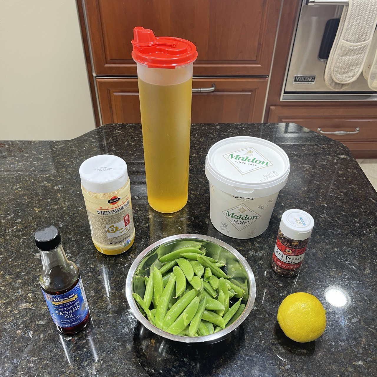ingredients for sautéed sugar snap peas: toasted sesame oil, sesame seeds, avocado oil, Maldon salt, crushed red pepper, a lemon, and 8 oz of sugar snap peas