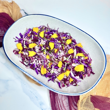 Purple Slaw with Red Cabbage, Radicchio, Red Onion, Beets, and Grapes. Garnished with Chives and Marigold Petals.