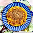 Mashed sweet potato in a blue serving bowl with sweet dukkah sprinkled on top