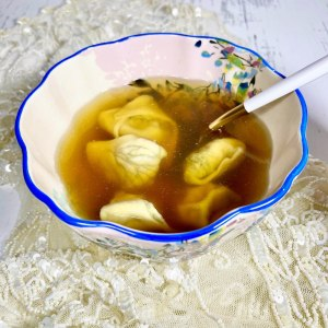 bowl of chicken soup with 5 dill-laminated kreplach