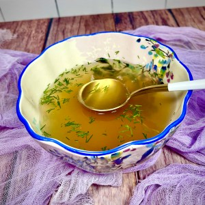 Vegan Jewish Penicillin in a floral bowl with a bright blue rim. The soup is garnished with finely chopped fresh dill. In the soup is a gold and white spoon. In the background is a white tile wall wooden countertop, and a lilac-colored gauzy fabric under the bowl