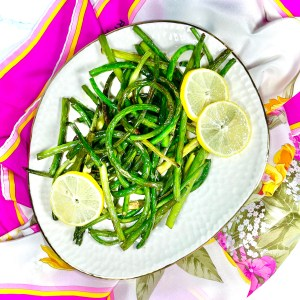 Lemon Brown Butter Garlic Scapes on a white asymmetrical plate, garnished with lemon slices, over a pink, yellow, orange, white, and green floral silk scarf.
