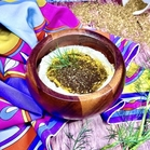 A small, wooden bowl filled with labneh, olive oil, za'atar, and sprigs of dill. In the background is spilled za'atar, a vibrantly colorful silk scarf, and a couple stems of dill