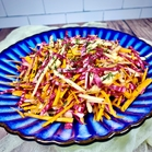 Close-up of Chioggia Beet Slaw with carrot, green apple, dill, and a light dressing of olive oil, lemon juice, Dijon mustard, maple syrup, and kosher salt. The slaw is served on a blue scalloped serving plate
