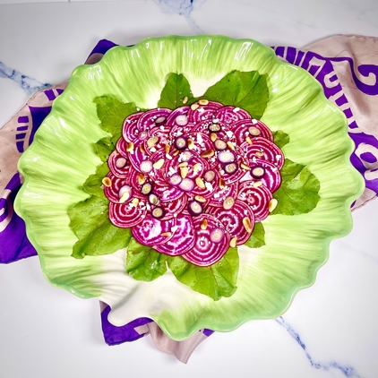 Chioggia Beet Carpaccio over a bed of beet greens, garnished with crumbled goat cheese, toasted pine nuts, purple scallions, and flaky Maldon salt. The dish is served on a large, round green serving plate that is shaped to look like a leaf of lettuce, and the serving plate is on a purple and beige silk scarf. The background is a white marble surface.