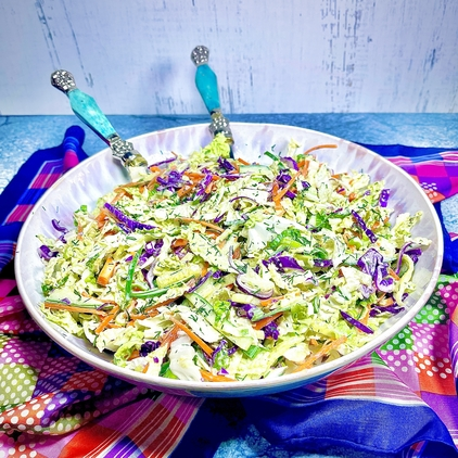 Cucumber Dill Coleslaw in a large mixing bowl with two serving spoons with turquoise handles nestled into the slaw. In the background is a colorful scarf on a granite surface