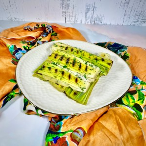 Braised leeks with charred grill marks, stacked in a square on a white plate with a gold rim. in the background is a colorful orange scarf on a pink and white marble countertop