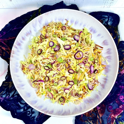 Miso Honey Apple Slaw with rainbow carrots, Napa cabbage, red onion, and purple scallions in a large white and lilac serving bowl. There is a dark colored velvet scarf in the background.