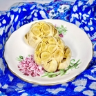 Roasted Garlic heads on a floral saucer, with a white and blue fabric background