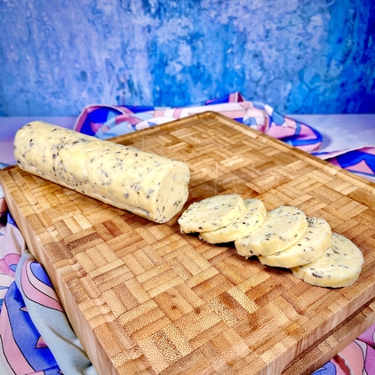 A half-sliced roll of garlic herb compound butter on a wooden chopping block, with a pastel background